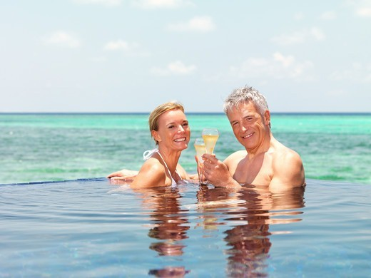 Portrait of romantic mature couple in pool with champagne by the sea : Stock Photo