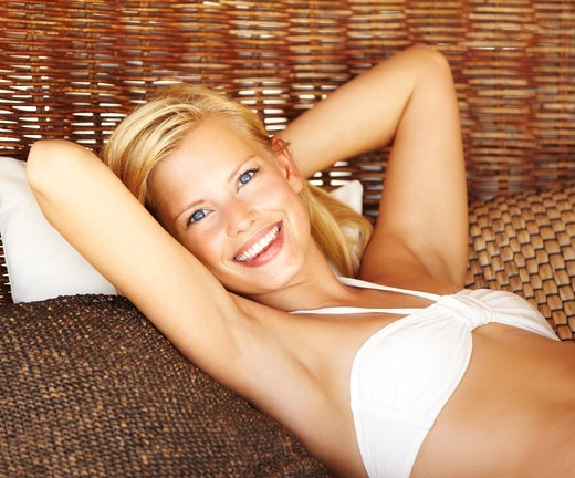 Stock Photo: 4197R-53815 Pretty blond female lying in a large comfortable beach chair