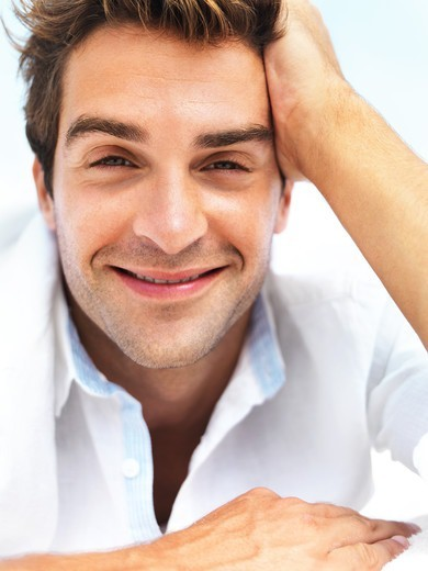 Portrait of a handsome man smiling with contentment : Stock Photo
