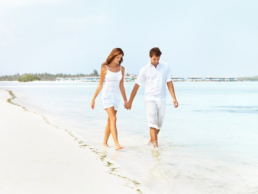 Stock Photo: 4197R-54211 Happy young couple walking along the seashore