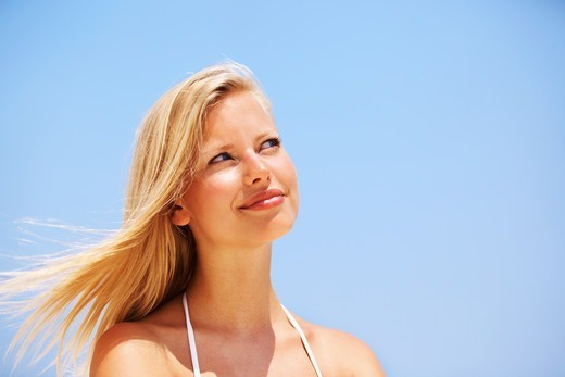 Stock Photo: 4197R-54359 Closeup of cute young woman smiling outdoors - copyspace