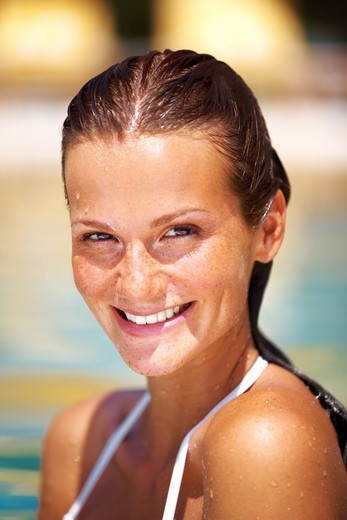 Stock Photo: 4197R-54713 Pretty young woman smiling while in a swimming pool