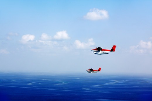 Stock Photo: 4197R-54742 Two seaplanes flying overhead with the blue ocean horizon as their background