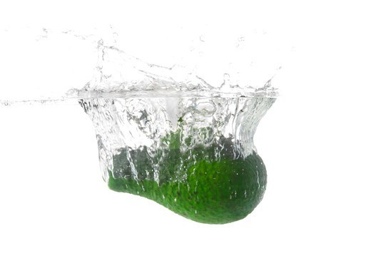 Green avocado deing dropped in water while isolated on white : Stock Photo