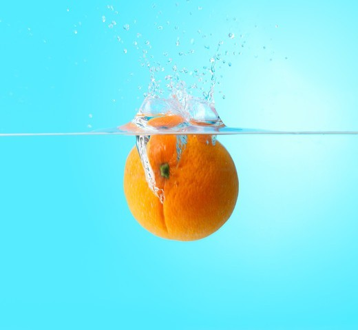 Juicy orange dropping into water and creating a little splash : Stock Photo