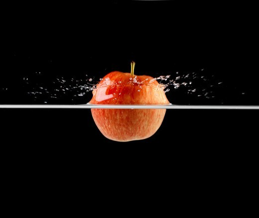 Stock Photo: 4197R-54835 Red apple breaking the waters surface as it is dropped - Isolated on black