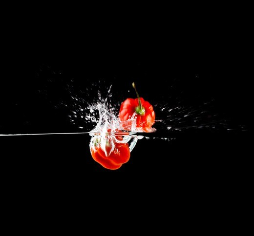 Stock Photo: 4197R-54837 Two red peppers being dropped into water while isolated on black
