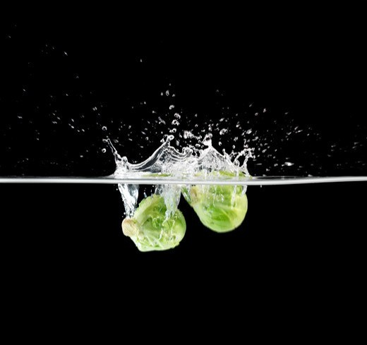 Healthy brussel sprouts breaking the surface of water as they are dropped - Isolated on black : Stock Photo