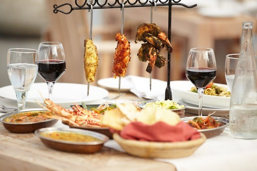 A selection of meats sitting invitingly upon a dining table with an assortment of food dishes : Stock Photo