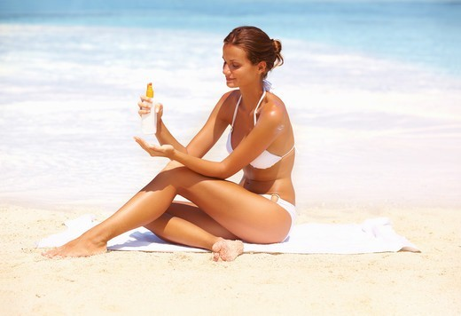 Portrait of beautiful woman applying suntan lotion at beach : Stock Photo