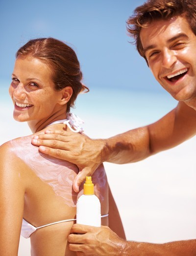 Portrait of happy young couple applying sun block lotion for preventing sunburn : Stock Photo