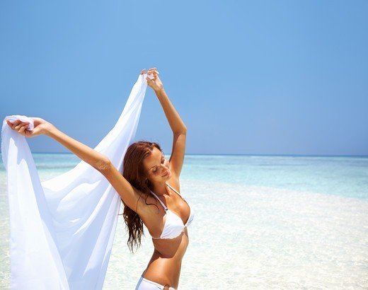 Portrait of peaceful woman holding sarong at beautiful beach : Stock Photo