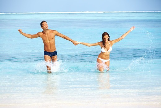 Stock Photo: 4197R-55195 Portrait of happy young couple enjoying together on beach