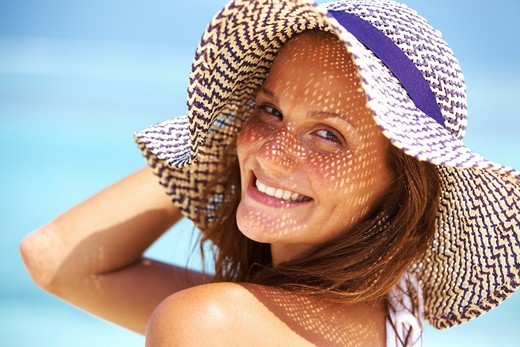 Stock Photo: 4197R-55265 Closeup of young woman enjoying summer at beach wearing hat