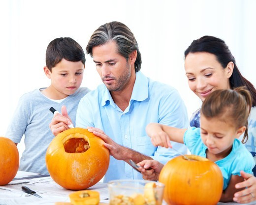 A young family making jack-o-lanterns for Halloween : Stock Photo