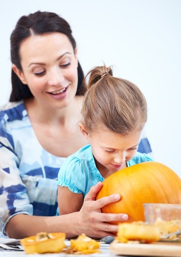 Stock Photo: 4197R-55439 A little girl looking inside her halloween jack-o-lantern