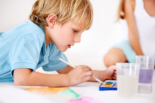 Close up picture of a young boy carefully mixing paints for his art project : Stock Photo