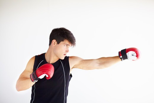 Young boxer punching while wearing gloves and isolated on white : Stock Photo