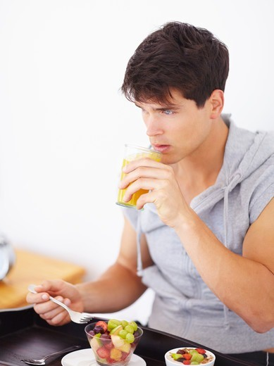 Handsome young guy enjoying a healthy fruit salad and juice : Stock Photo
