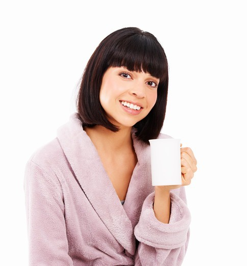 Stock Photo: 4197R-55955 Cute young woman enjoying a fresh cup of coffee in her dressing gown