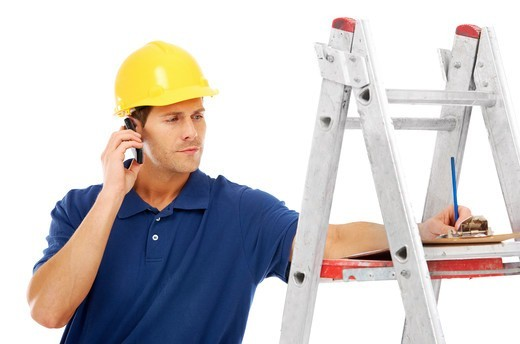 Stock Photo: 4197R-56023 A young handyman talking on the phone while standing on a ladder