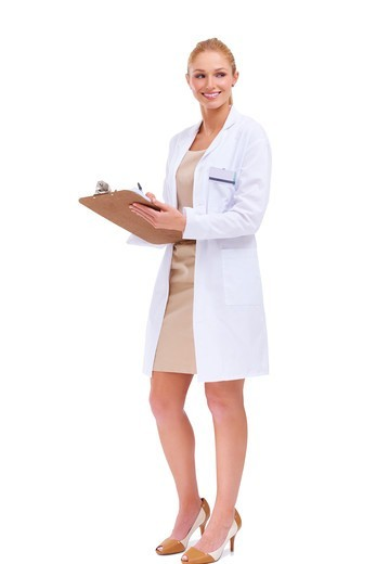 Stock Photo: 4197R-56514 Beautiful female doctor glances sideways while smiling and holding a clipboard