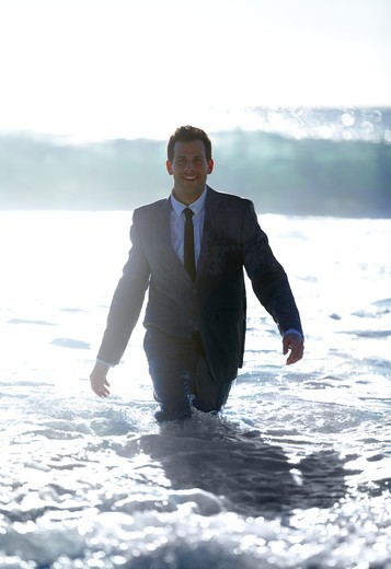 A business man walks through the rushing water toward the camera : Stock Photo