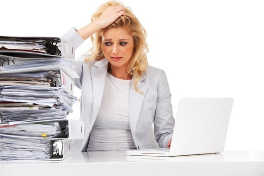 Stock Photo: 4197R-56957 An overworked businesswoman looking anxiously at a pile of files next to her - Isolated