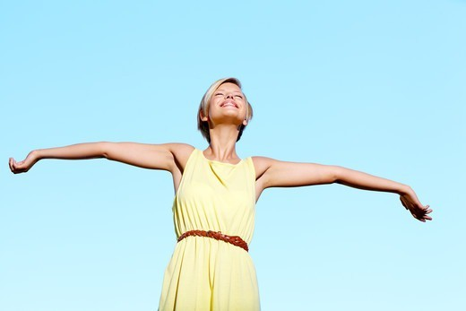 A pretty young woman standing with her arms raised with a blue sky in the background : Stock Photo