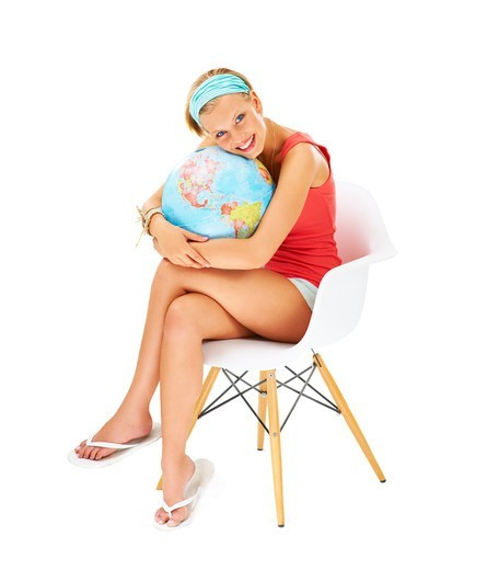 Stock Photo: 4197R-57312 Smiling young woman holding tightly onto a globe of the world