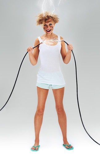 Stock Photo: 4197R-57317 Untidy looking young woman holding power cables after receiving an electric shock