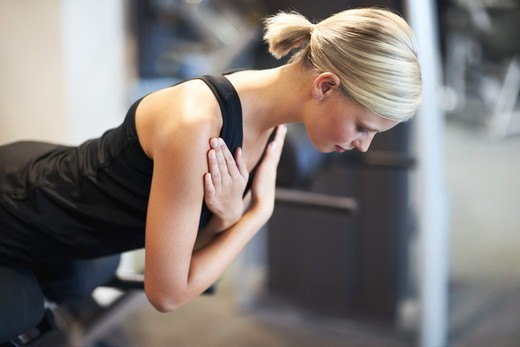 Profile of an attractive young woman working her abs in the gym : Stock Photo