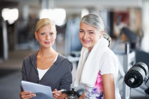 Portrait of a stunning female gym instructor helping an older woman : Stock Photo