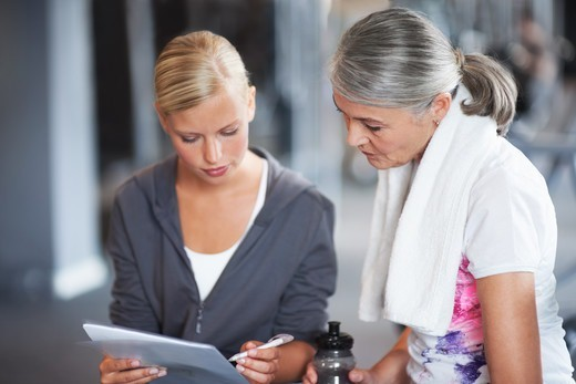 Stock Photo: 4197R-57734 A beautiful young female gym instructor helping an older woman