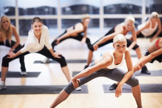 Portrait of a beautiful young woman leading an aerobics class : Stock Photo