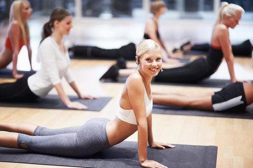 A stunning young woman taking her aerobics class through some stretches : Stock Photo