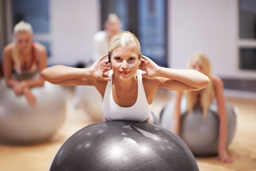 Stock Photo: 4197R-57776 Portrait of a beautiful young woman working with her aerobics class using exercise balls