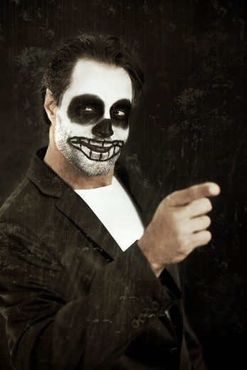 Stock Photo: 4197R-58104 A man with his face painted like a skull for halloween pointing on a black background