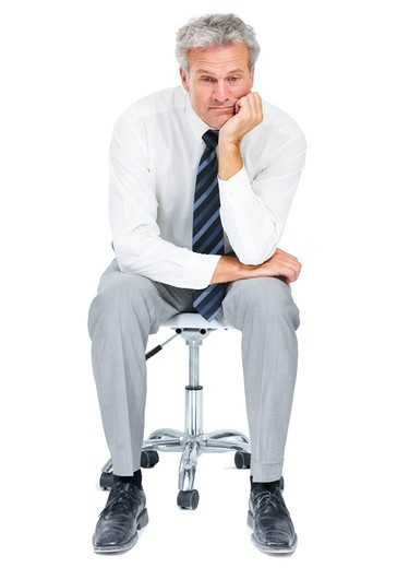 Stock Photo: 4197R-58147 A dishevelled executive reflecting on life while sitting in an office chair - Isolated