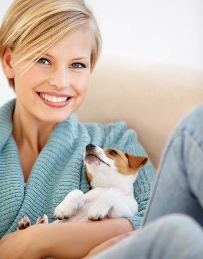 Stock Photo: 4197R-58351 An attractive young female relaxing on the couch with her puppy