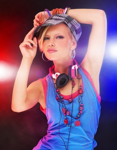Stock Photo: 4197R-58404 Trendy young girl in urban attire giving you attitude against a background of colored lights