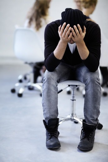 Stock Photo: 4197R-58470 A young man holds his head in his hands while taking a moment for himself in a therapy session