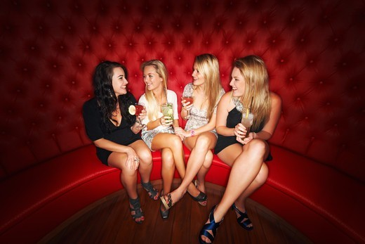 Stock Photo: 4197R-58563 Four beautiful girls enjoying cocktails in a booth at an elite club