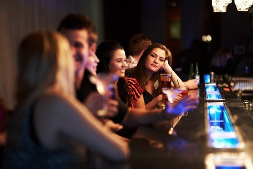 Stock Photo: 4197R-58618 Portrait of a pretty young woman leaning on her hand at the bar while others converse