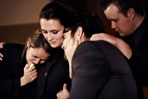 A family crying at a funeral service in a church : Stock Photo