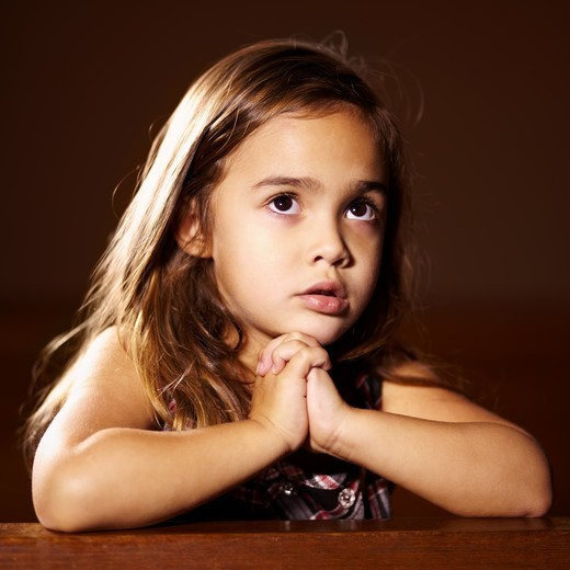 Stock Photo: 4197R-58706 A cute little girl with her hands together praying in church