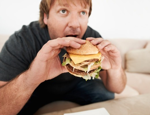 A mature man biting into a hamburger : Stock Photo