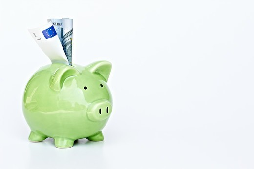 Stock Photo: 4197R-58808 A piggybank with money in the slot