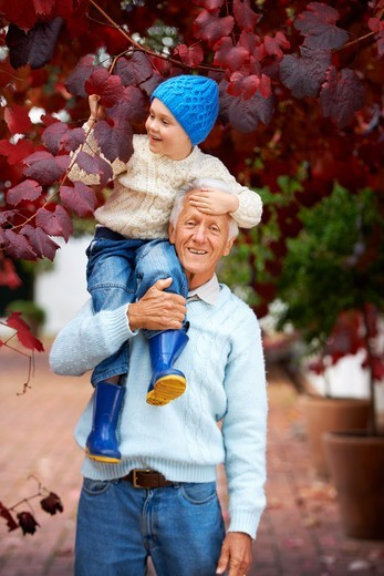 A grandfather holding his grandson on his shoulder outside : Stock Photo