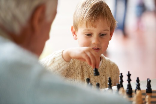 Stock Photo: 4197R-58909 A grandfather playing chess with his grandson